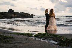 Wedding lovestory, just married couple near the ocean at sunset Stock Images