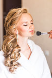 Wedding makeup artist making a make up for bride. Beautiful sexy model girl indoors. Beauty blonde woman with curly hair Stock Photo