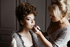 Wedding makeup artist making a make up for bride. Beautiful model girl indoors. Beauty women with curly hair. Female portrait. Bridal morning of a cute lady royalty free stock photo