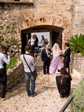Wedding at Malcesine Castle, Lake Garda, Italy. A bride, her father and the groom during a wedding ceremony at Malcesine Castle, with two photographers and a Royalty Free Stock Images