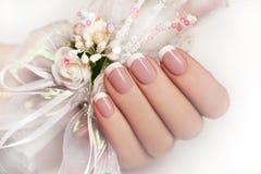 Wedding manicure. NWedding manicure on female hand with festive decoration of white ribbons and flowers stock photos