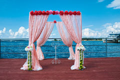 Wedding in marine style in coral color. Wedding ceremony in marine style in coral color with ship on background Stock Images