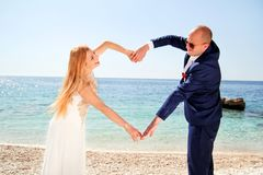 Wedding married couple of hands make a real heart Stock Photos