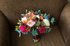 Wedding marsala bouquet with roses and other flowers on brown ar Royalty Free Stock Photography