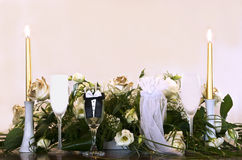 Wedding Memories. Wedding arrangement consisting of some candles, glasses covered with bridegroom suit, bride's wedding dress and floral arrangement stock photo