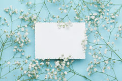 Wedding mockup with white paper list and flowers gypsophila on blue table from above. Beautiful floral pattern. Flat lay style. Wedding mockup with white paper