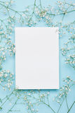 Wedding Mockup With White Paper List And Flowers Gypsophila On Blue Background From Above. Beautiful Floral Pattern. Flat Lay. Royalty Free Stock Image