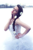 Wedding model. Outdoors portrait of young beautiful female model in white wedding dress with flowers in her hair Stock Photos