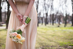 Wedding moment. A woman wearing a long dress and holding a bouquet of flowers, seen from behind Royalty Free Stock Photography