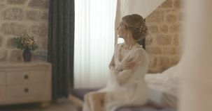 Bride in delicate silk robe. Wedding at Montenegro. Traditional European  ceremony. Morning before the reception. 4k. Thoughtful c41c317b2