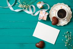 Wedding morning concept. Invitation card, heart-shaped chocolate, gift box, cup of coffee, daisy flowers. Stylish minimal women`s