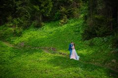 Wedding in mountains, a couple in love, in mountain forrest, standing on the path, among the lawn with the green grass, rustic sty Royalty Free Stock Photo