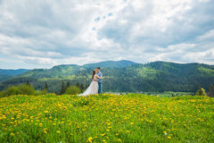 Wedding in mountains, A COUPLE IN LOVE, MOUNTAINS background, STANDING surounded dandelions, AMONG THE LAWN WITH THE GREEN GRASS, Stock Image