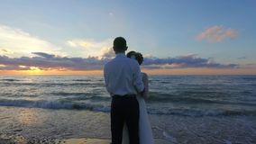 Wedding. Newly married couple on the beach at amazing sunset. stock video footage