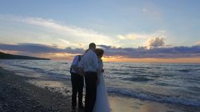 Wedding. Newly married couple on the beach at sunset talking with camera man. stock video footage