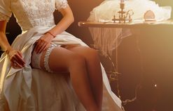 Wedding night preparing garter. Bride undressing. Stock Photo