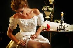 Wedding night preparing garter. Bride undressing. Stock Images