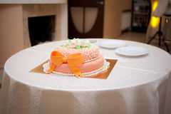 Wedding orange cake with ribbon. On the table Royalty Free Stock Photography