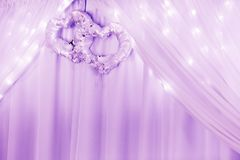 Wedding ornament with two hearts and curtain and lights. Colored in purple royalty free stock photography
