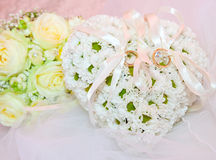 Wedding ornaments, ring on pillow in shape of heart Stock Photography