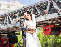 Wedding pair hugging and kissing on fire truck Stock Photo