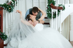 Wedding pair, kiss on stairs. Veil Royalty Free Stock Images