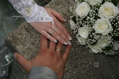 Wedding. The palms of the bride and groom with a bouquet of flowers Stock Images