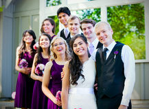 Wedding party standing outdoors with bride and groom Stock Images