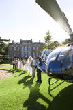 Wedding party watching bride and groom walking towards helicopter (lens flare) royalty free stock image