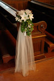 Wedding pew bow. With white organza and white lilys on a wood church banch Royalty Free Stock Photography