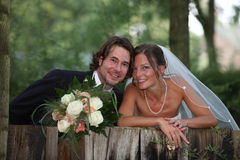 Wedding photo with bouquet. Young beautiful couple is standing behind a wood wall. bride is carrying the bouquet flowers. both are looking direclty into the cam Stock Photo