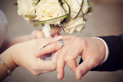 Wedding photo. Wedding rings, hand and flowers in the wedding photo Stock Photo
