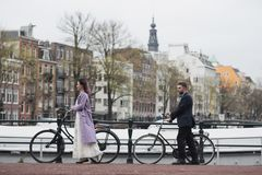 Wedding photo shooting. Bride and bridegroom walking in Amsterdam. Stand with bicycles near the canal. Wedding photo shooting. Bride and bridegroom walking in royalty free stock image
