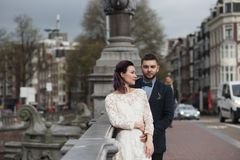 Wedding photo shooting. Bride and bridegroom walking in Amsterdam. Stand on bridge and hug. Wedding photo shooting. Bride and bridegroom walking in Amsterdam stock images