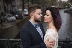 Wedding photo shooting. Bride and bridegroom walking in Amsterdam. Stand on bridge and hug. Wedding photo shooting. Bride and bridegroom walking in Amsterdam stock image