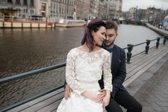 Wedding photo shooting. Bride and bridegroom walking in Amsterdam. Stand on bridge and hug. Wedding photo shooting. Bride and bridegroom walking in Amsterdam royalty free stock photo