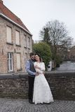 Wedding photo shooting. Bride and bridegroom walking in Brugge. Stand on bridge and hug. Wedding photo shooting. Bride and bridegroom walking in Brugge, Belgium stock image
