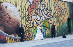Wedding Photographer & Clients in front of Graffiti Wall. Royalty Free Stock Photo