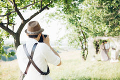 Wedding photographer takes pictures of bride and groom in nature, fine art photo Royalty Free Stock Photo