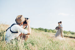 Wedding photographer takes pictures of bride and groom in nature, fine art photo Royalty Free Stock Photos