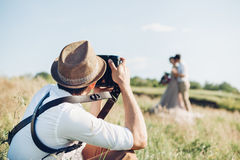 Wedding photographer takes pictures of bride and groom in nature, fine art photo Royalty Free Stock Photography
