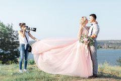 Wedding photographer takes pictures of bride and groom. In nature. wedding couple on photo shoot. photographer in action royalty free stock image