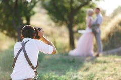 Wedding photographer takes pictures of bride and groom royalty free stock photos