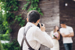 Wedding photographer takes pictures of couple in love in nature in summer. Wedding photographer takes pictures of a couple in love in nature in summer Royalty Free Stock Photography