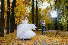 Wedding photographer is taking pictures the bride. In the autumn park Stock Image