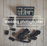 Wedding photographer work tools flat lay. Top view on photo cameras with equipment, smartphone, bundle of money and laptop with wedding photos on light wooden Stock Photo