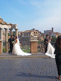 Wedding Photos in Rome. Two couples pose for their wedding photos in front of the Forum in Rome, Italy, a city known for romance and love royalty free stock photos