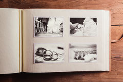 Wedding photos on a table. Wedding photos in album. Studio shot on wooden background royalty free stock image