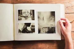 Wedding photos on a table. Wedding photos in album. Studio shot on wooden background stock image
