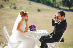 Wedding Phtographer and Model. Groom photographer and bride model at table Royalty Free Stock Photography
